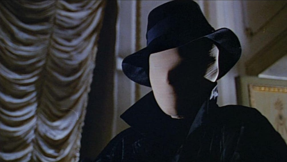 The killer from Blood and Black Lace, wearing a white face mask and a black fedora.