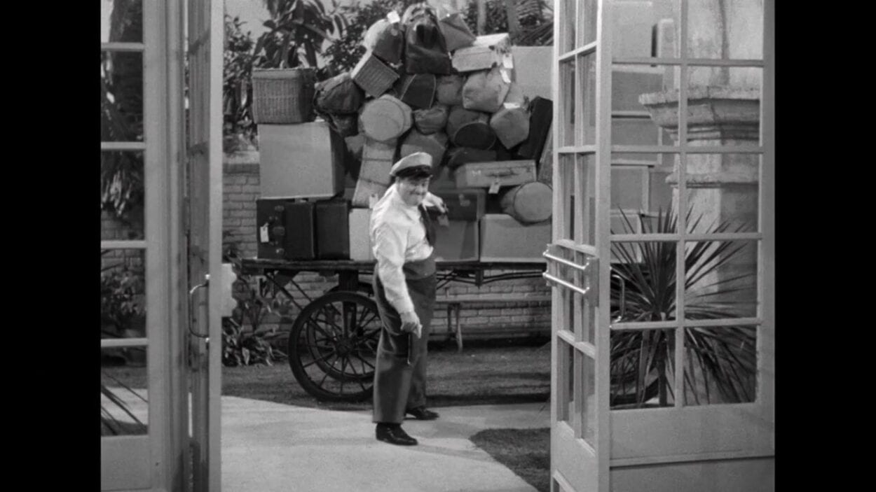"""Wilbur Grey (Lou Costello) pulls a grip out of a pile of baggage in the film, """"Abbott and Costello Meet Frankenstein"""" (1948)."""