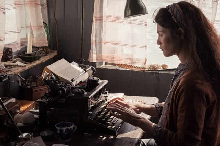 Alice types her latest writing on a typewriter by a window.