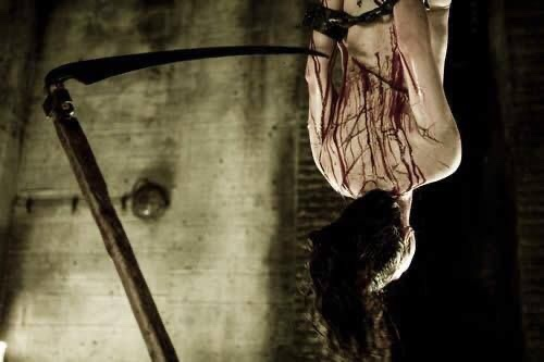 Lorna is suspended upside down while being cut with a sickle to be used for a blood bath.