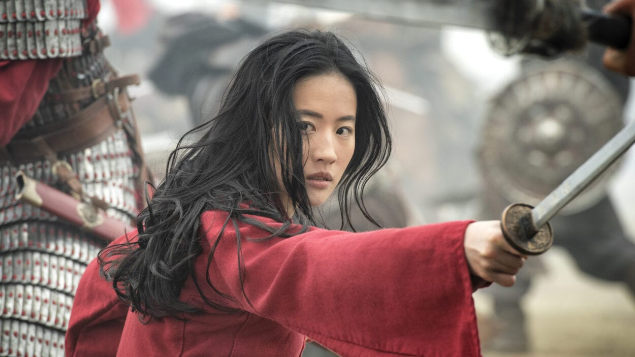 Mulan, with sword drawn, peers to her right at an adversary.