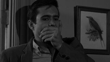 Norman Bates, hand over his mouth, standing against the door frame.