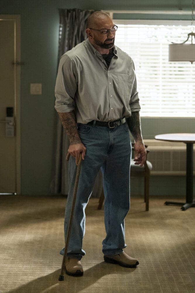 Doug stands in Room 104 with a cane