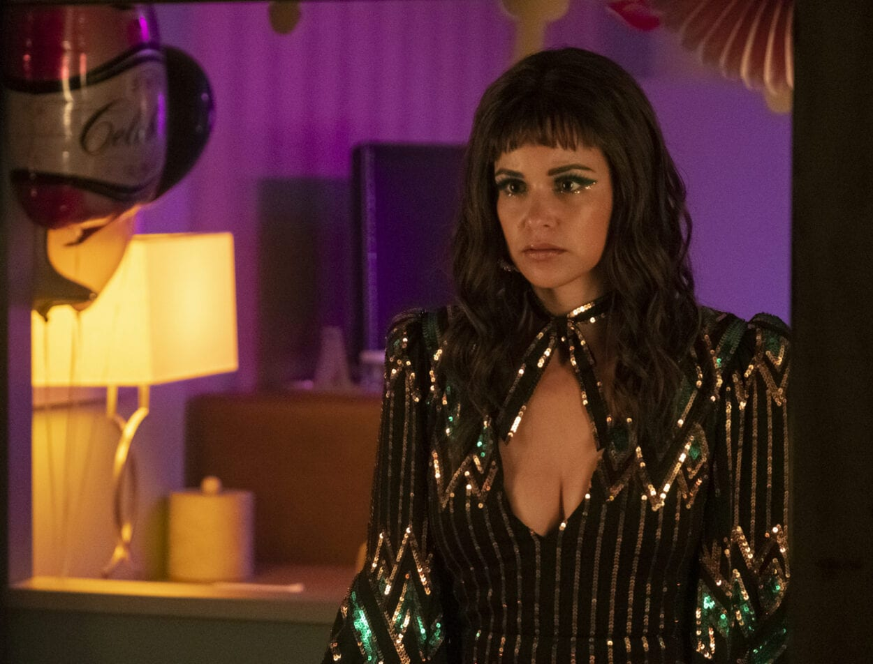 Eva looks in the mirror at her bangs and '70s style dress