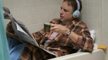 Harry lounging in the bathtub in a robe and earmuffs reading a newspaper