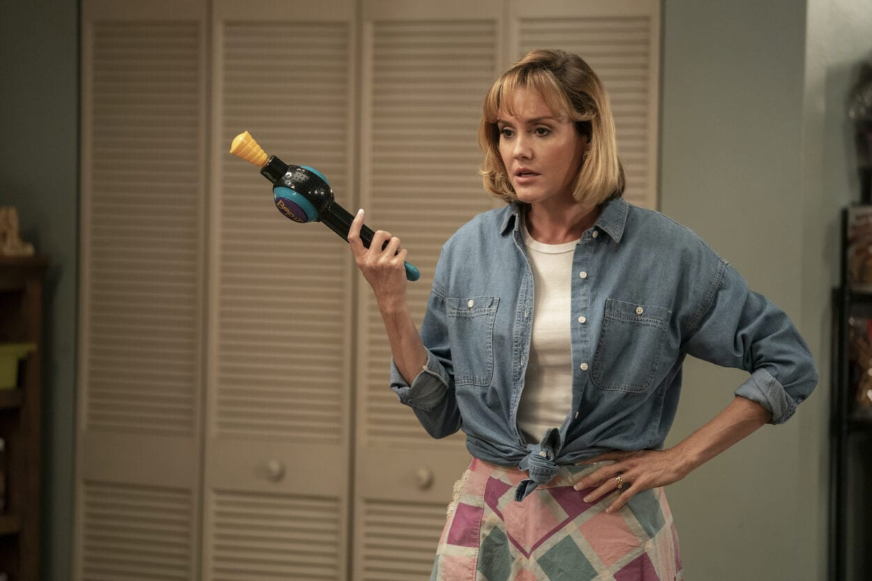 Linda holding up a Bop-It wearing an expression of disapproval