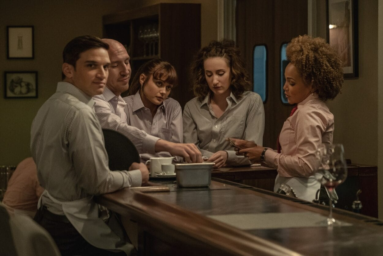Will, Sasha, Tess, Ari, and Heather sit around a table drinking while in uniform.