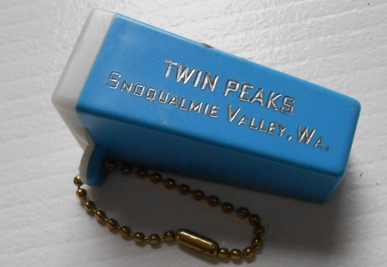 "blue single slide rectangular viewer the size of a keychain, embossed with ""Twin Peaks Snoqualmie Valley, Wa"" in gold."