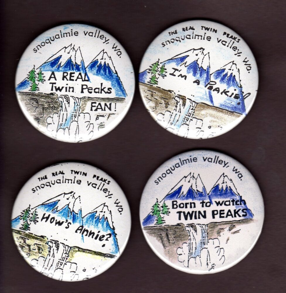 handmade Twin Peaks buttons, painted mountains with writing on them.