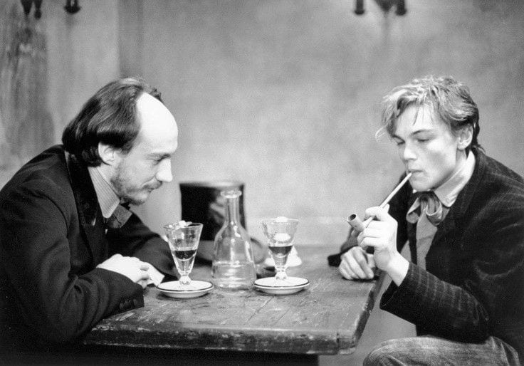 Arthur Rimbaud and his mentor and lover Paul Verlaine sit across a table from one another