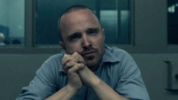 Warren (Aaron Paul) leans with his head towards his hands in Truth Be Told