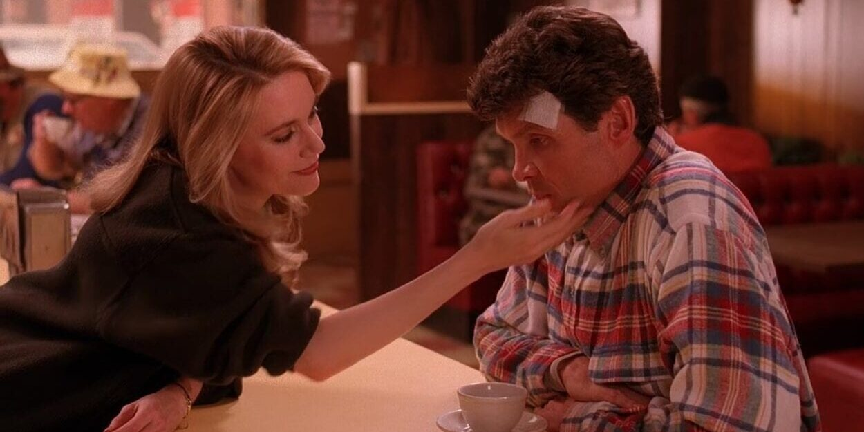In the Double R Diner, Norma reaches over the counter and lovingly touches Ed's face. Ed has a bandage on his head and looks concerned.