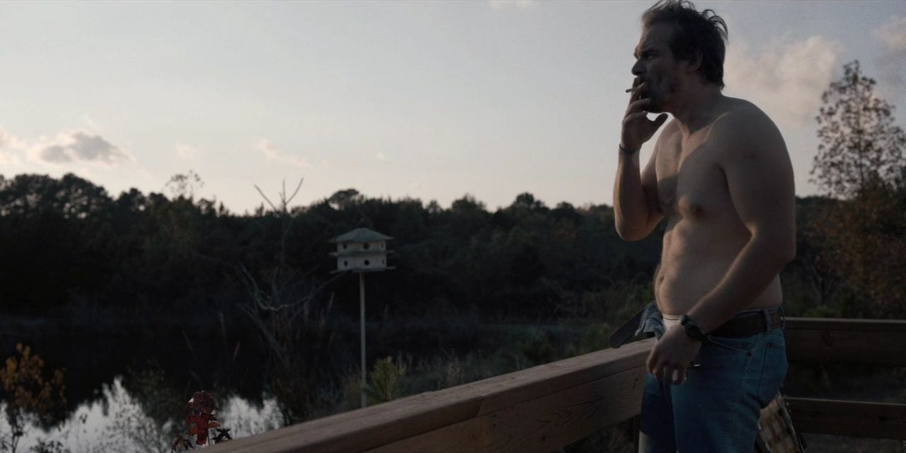 Hopper, half-dressed, smokes a cigarette outside looking out over the lake