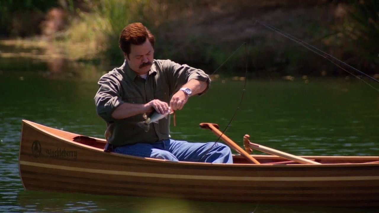 Ron sits in a small boat on a lake, taking a fish he just caught off the fishing line.