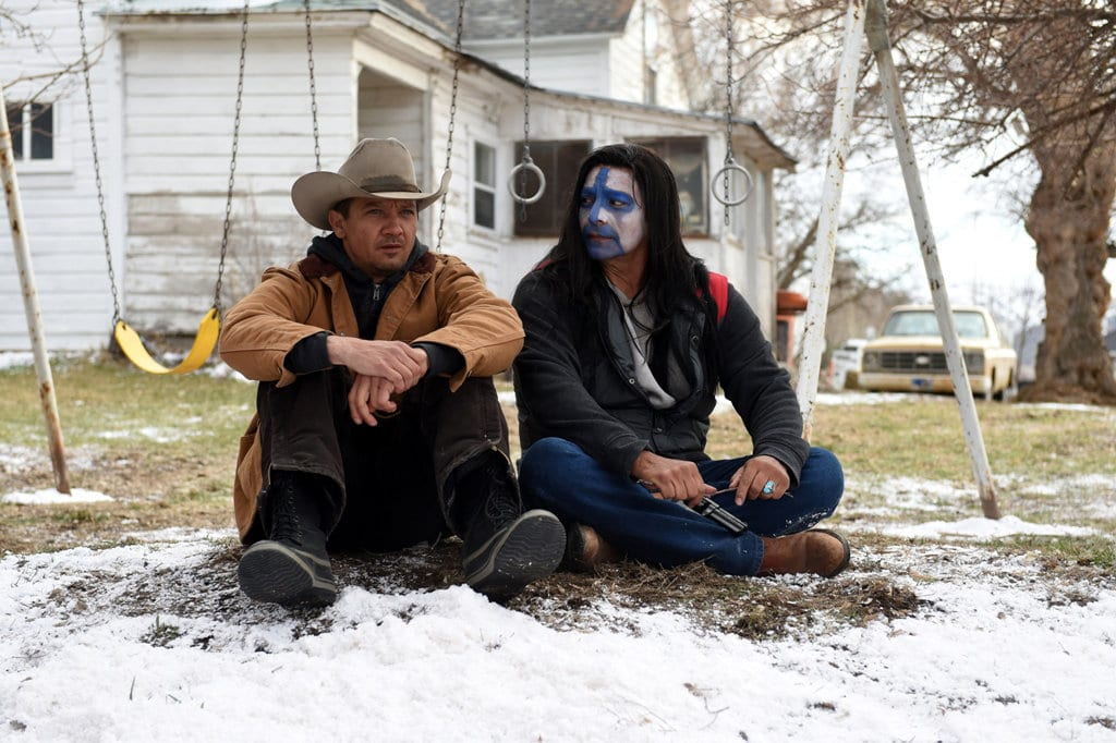 Jeremy Renner and Gil Birmingham sit on the ground in front of a swingset in Wind River