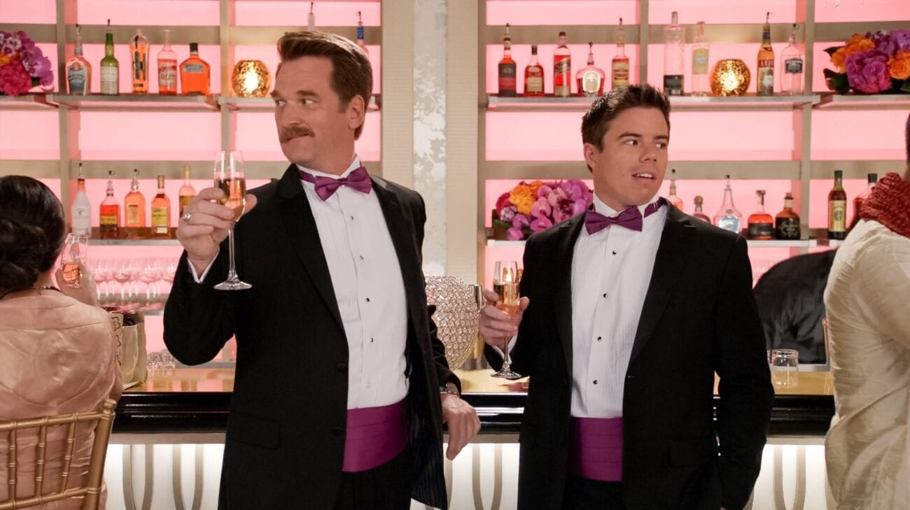 Darryl and White Josh wear tuxedos and stand at a bar with cocktails