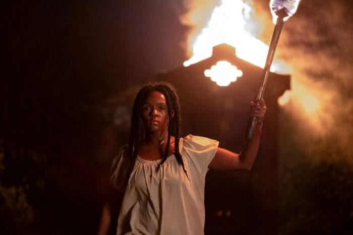 Eden stands with a torch in front of a shanty on fire in defiance.