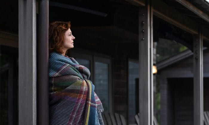 Lily stands on her porch wrapped in a blanket and looking towards the beach.