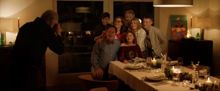Paul steps back to take a family picture at dinner with everyone around Lily.