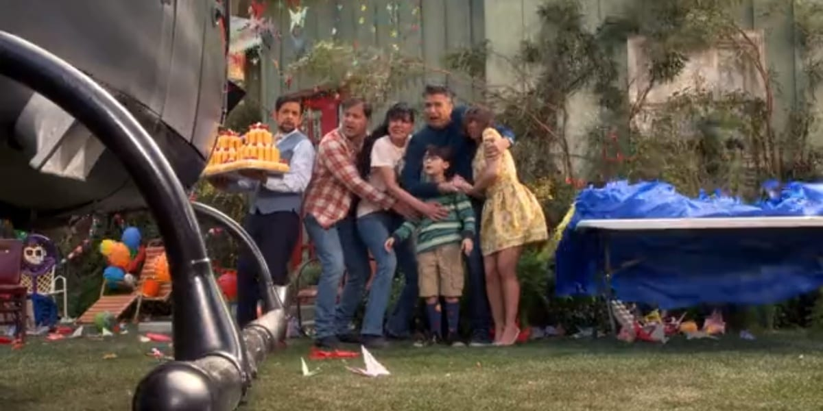 Left to right: Luis holding a cake made of Twinkies, Barry, Jackie, Javier, Elizabeth, Sammy in front of Javier, as they kneel slightly and look winded due to the arrival of a helicopter in the backyard in Broke