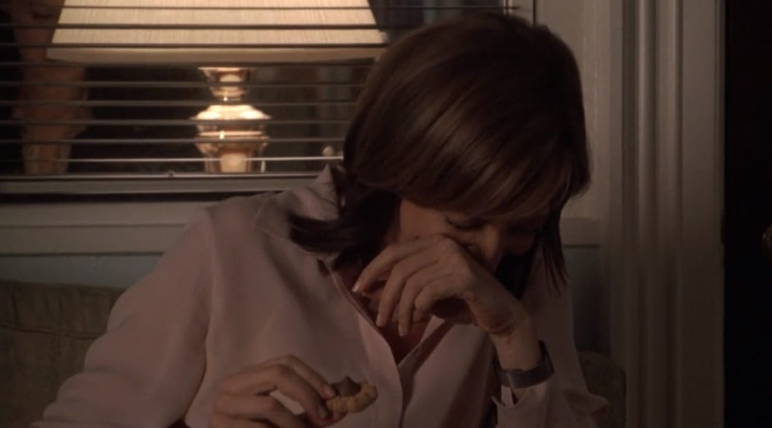 CJ sitting on a couch in her office laughing with her face behind one of her hands while holding a cookie in her other hand.
