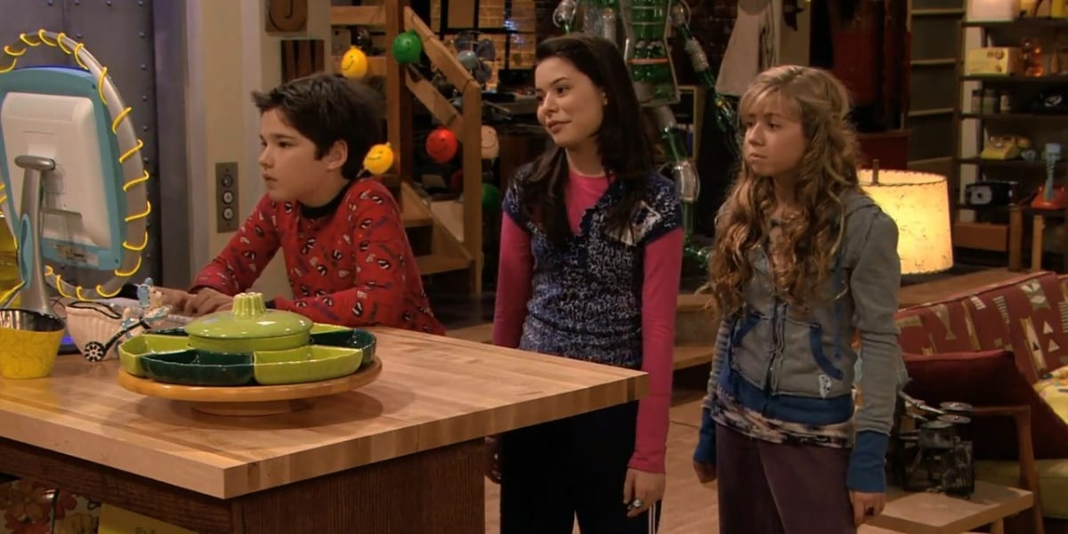 Freddie sitting and looking at the computer, Carly and Sam standing behind him in iCarly