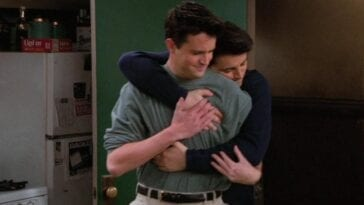 Joey hugs Chandler from behind in Friends, Chandler smiling slightly