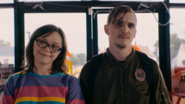 Patty (Emily Skeggs) and Simon (Kyle Gallner) standing in a fast food joint. Patty is smiling while Simon scowls.