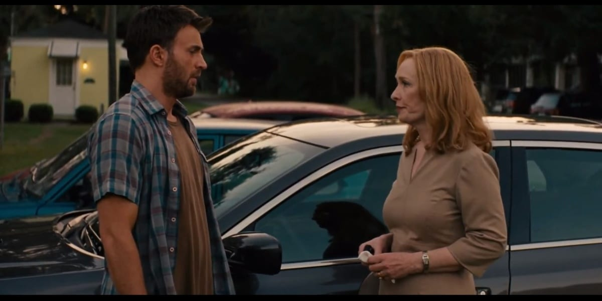 Frank and Evelyn standing before one another, a car in the background, Evelyn holding a handkerchief in one hand looking less than pleased as she looks at Frank, who wears a tired but firm look upon his face