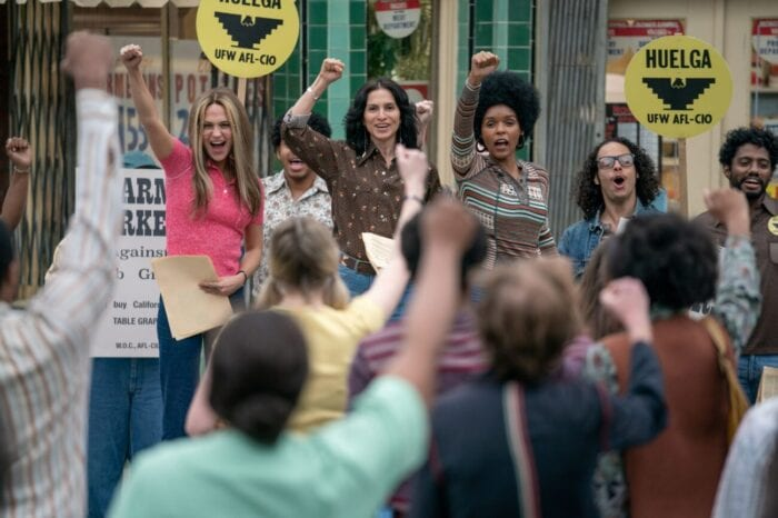 Gloria, Delores, and Dorothy raise their fists during a protest