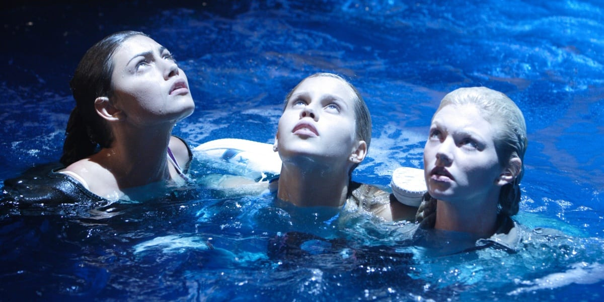 Cleo, Emma and Rikki looking up as the moonlight shines on them in the water, their faces expressions of confusion, in H20: Just Add Water