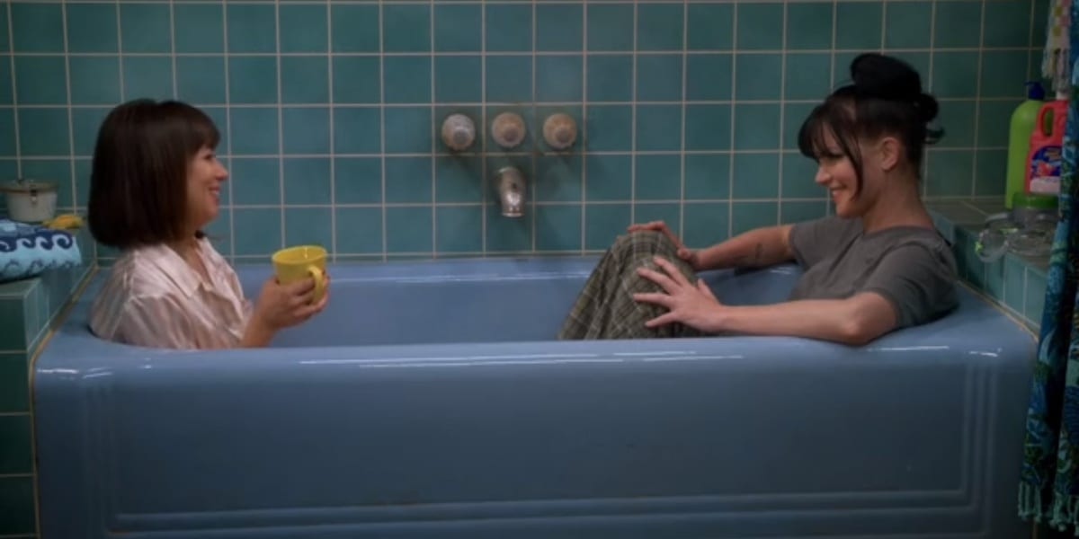 Elizabeth holding a cup of tea and Jackie sitting opposite from her in a blue bathtub in Broke