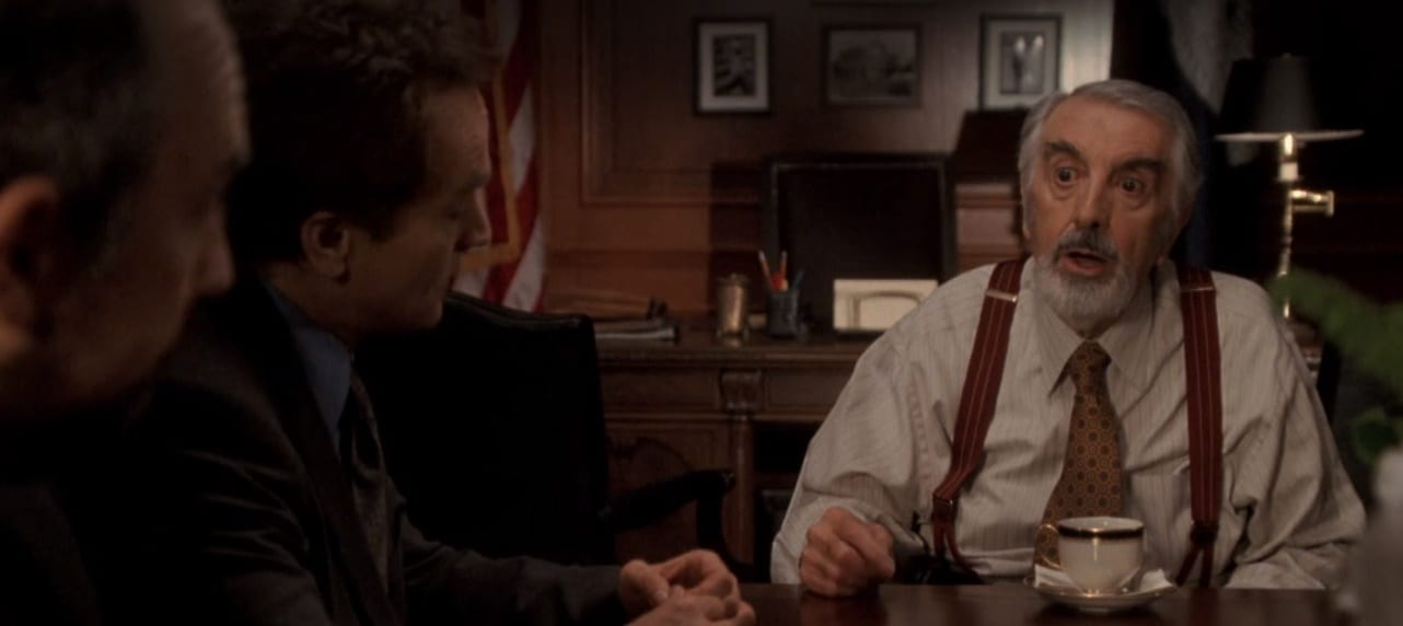 Toby and Josh sit at a table with a startled Chief Justice Ashland in the center of the frame.
