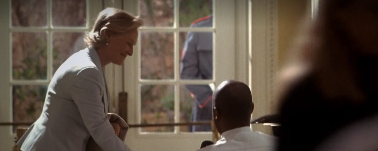Judge Evelyn Baker Lang (Glenn Close) signing out with a security guard in the White House lobby in front of glass paned double doors.