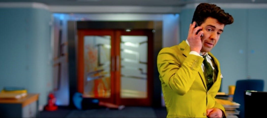 Lee in his yellow suit making a phone call