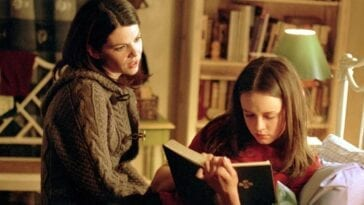 Lorelai sitting on the bed, talking to Rory, who's reading a book in Gilmore Girls