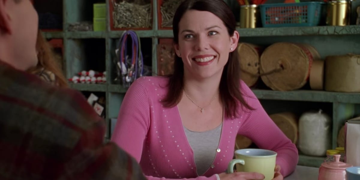 Lorelai smiling, wearing pink cardigan in Gilmore Girls pilot