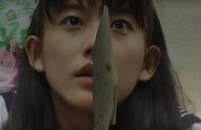 Hisayo holds up a garden shovel in self defense.
