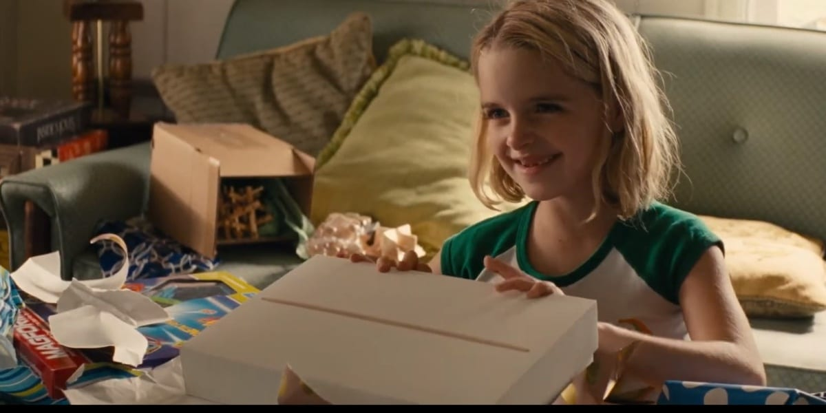 Mary happily opening gifts with a smile, a couch in the background, in Gifted