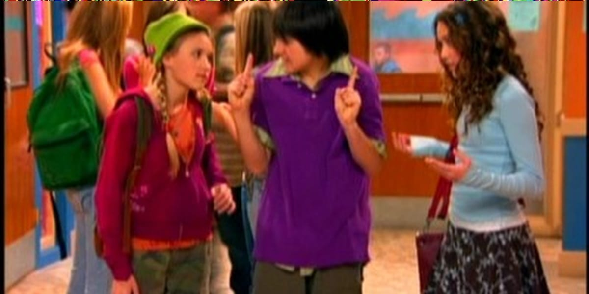Lilly on the left and Miley on the right of Oliver, both looking at him expectantly, while he looks nervous and holds up his fingers in Hannah Montana