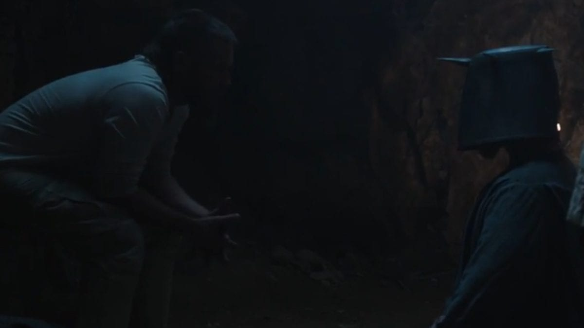 Caleb sits in front of a kneeling Otho in the cave