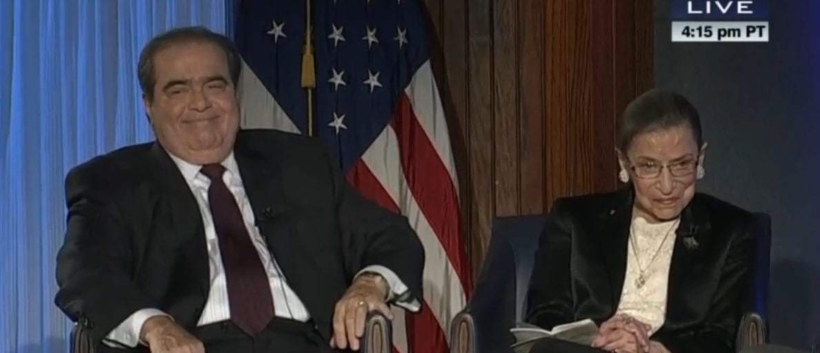 Justice Antonin Scalia and Justice Ruth Bader Ginsburg sitting in chairs with an American flag behind them.