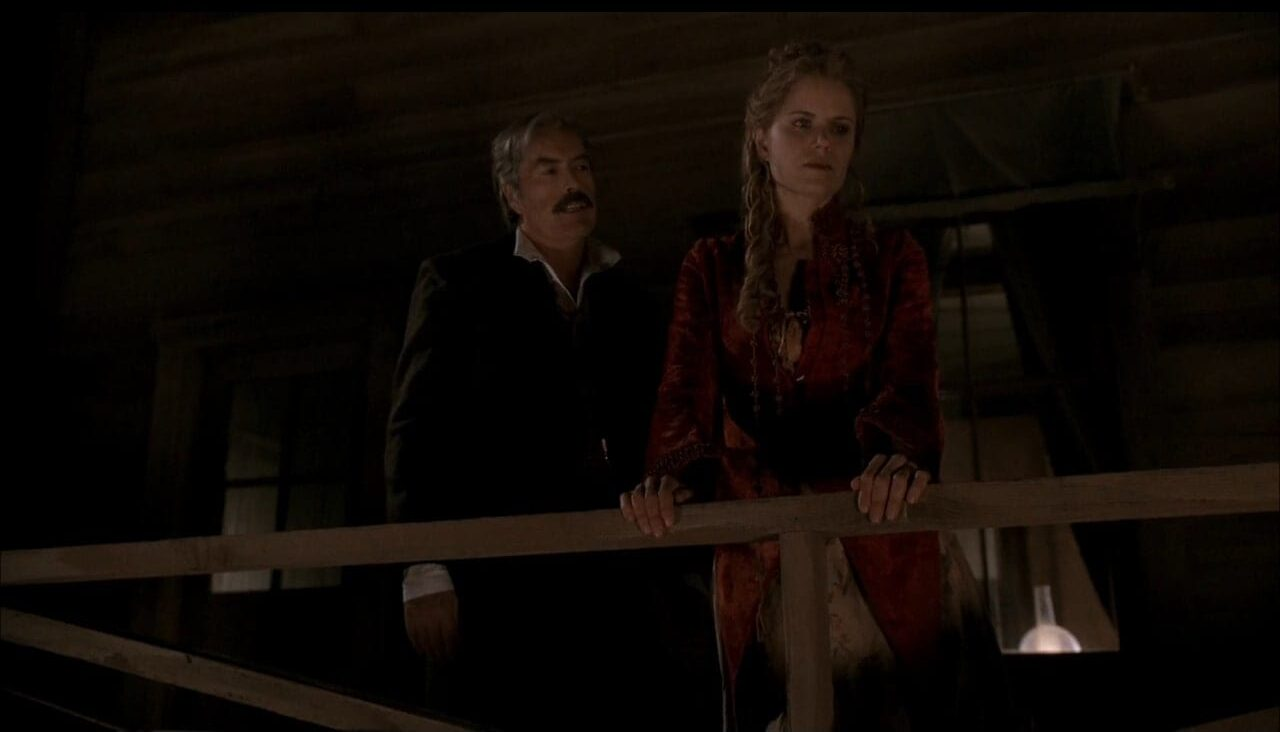 Cy (Powers Boothe) checks in on Joanie (Kim Dickens) in a scene from Deadwood.