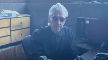 David Lynch sits at his desk wearing dark sunglasses