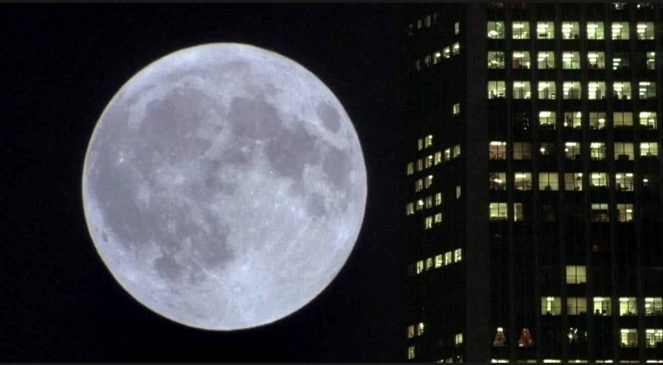 A long shot of the moon rising on the left side of an illuminated skyscraper.