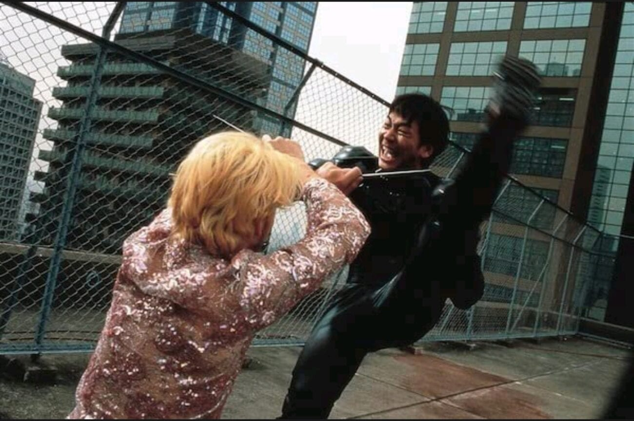 A dutch angle medium shot of Kakihara (Tadanobu Asano) holding out his arms to block his face from Ichi's (Nao Ohmori) bladed boots during a downward kick