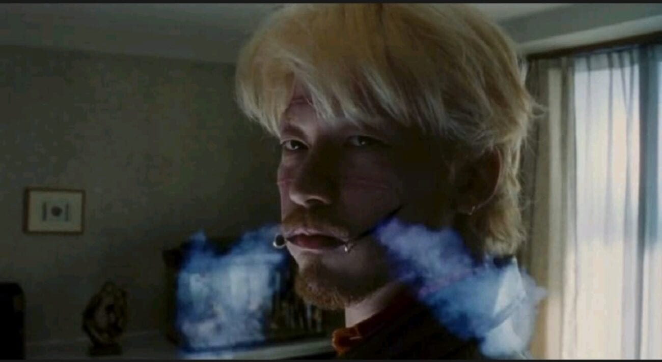 A medium shot of Kakihara (Tadanobu Asano) as smoke comes out from the facial scars on the side of his mouth