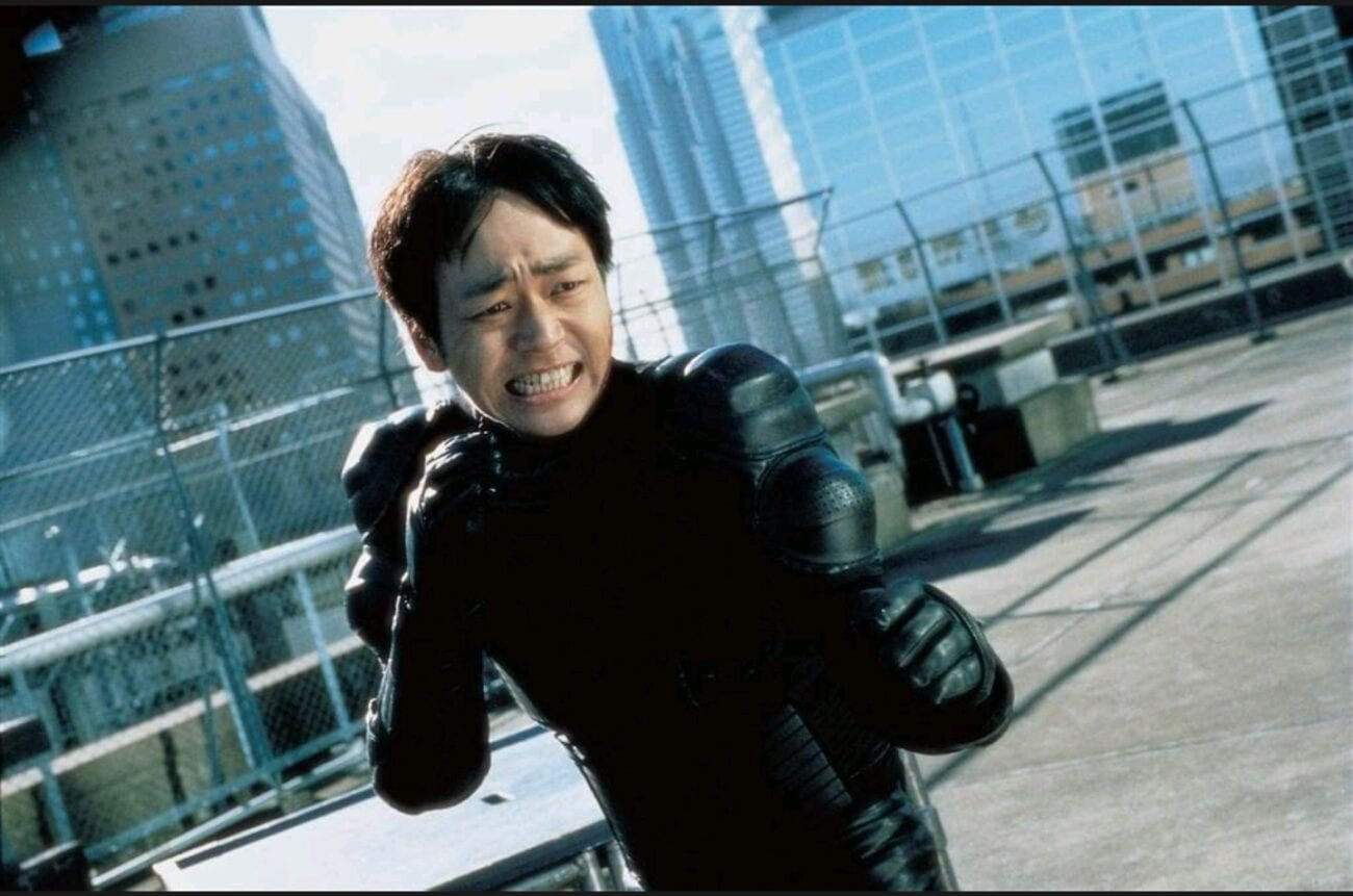 A dutch angle medium-shot of a grimacing Ichi (Nao Ohmori) as he holds his fists to fight