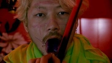 A close-up shot of Kakihara (Tadanobu Asano) as he holds open his pierced tongue while holding a blade on it with his other hand.