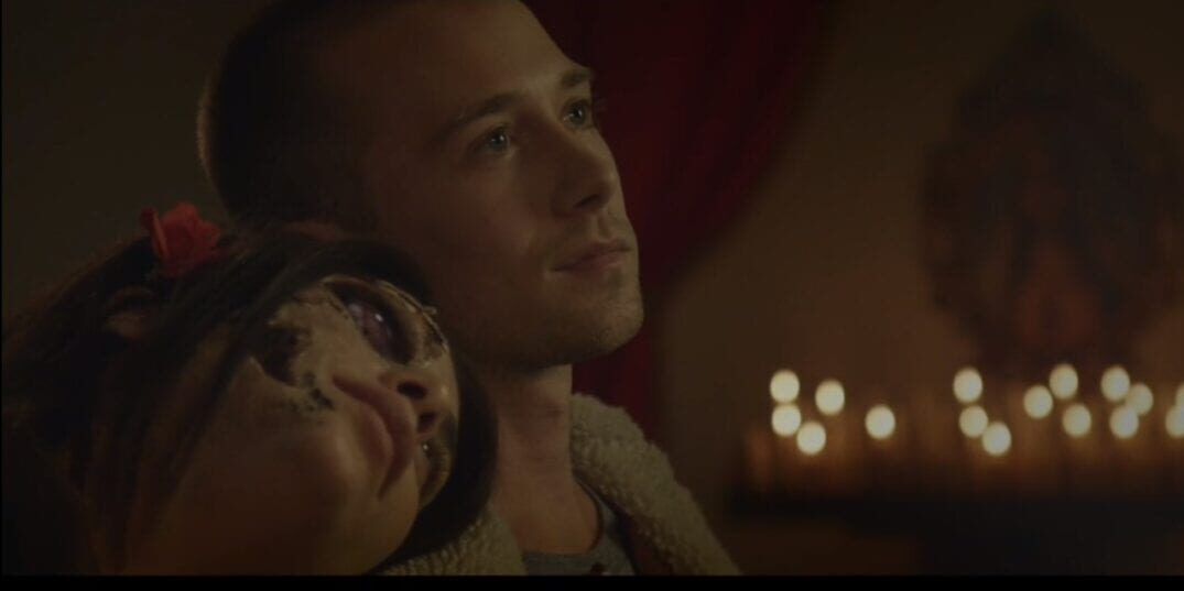 Louise rests her head on Evan's shoulder as her face decays
